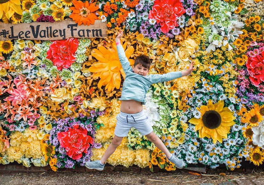Child jumping in front of a flower wall