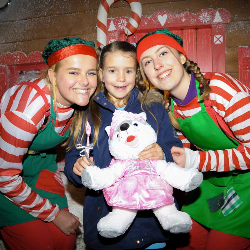 Elves with smiling little girl at Christmas